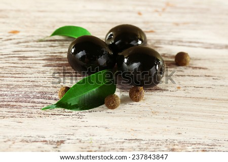 Tree black olives with leaf and peas on painted wooden background - stock photo