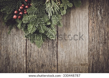 Tree branch with Holly Berry on rustic wooden background used for christmas decoration - stock photo