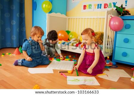 Tree kids drawing on the floor in bedroom - stock photo