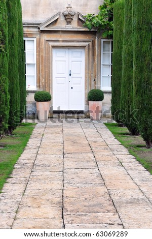 Tree Lined Garden Path Leading to a Stately Home - stock photo