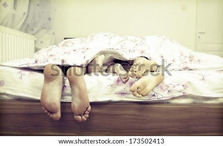 Tree pairs of legs of the happy family in bed - father, mother and baby  - stock photo