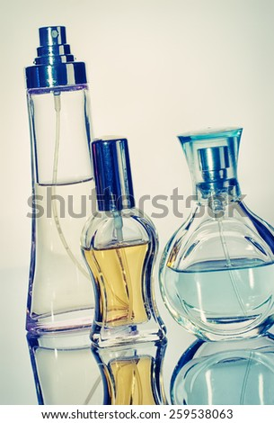 Tree perfume bottles with reflection sepia style vintage look - stock photo