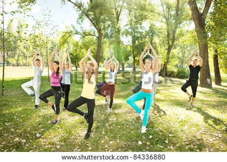 tree position,  large group of young people doing yoga, outdoor - stock photo