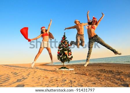 Tree Sexy Santos  have a fun at the beach.  (concept: Tropical winter fun) - stock photo