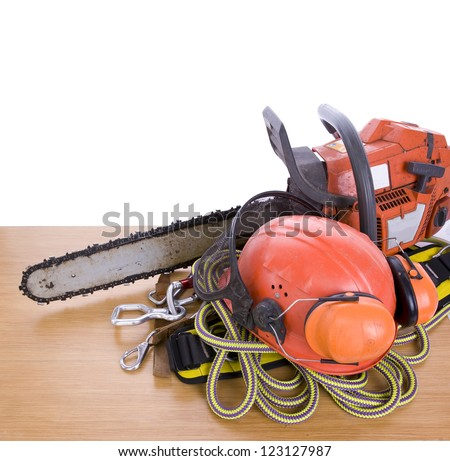 tree surgeon tools including chainsaw, helmet, harness, ear defenders and rope on desk - stock photo
