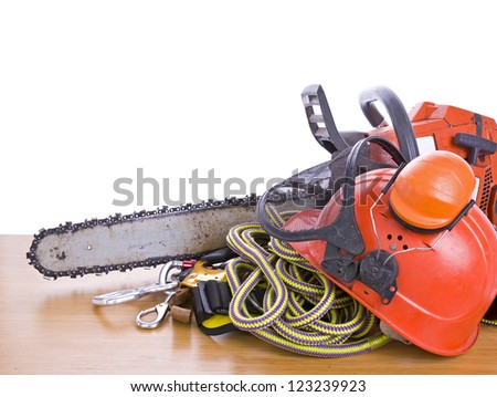tree surgeon tools on desk including chainsaw, helmet, harness, ear defenders and rope - stock photo