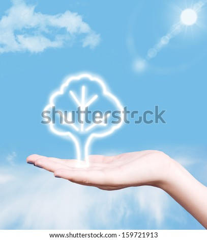 Tree symbol in human hand against blue sky. Green planet concept. - stock photo