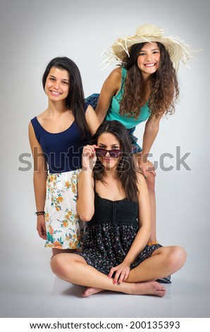 Tree teenager girls best friends posing in the studio - stock photo