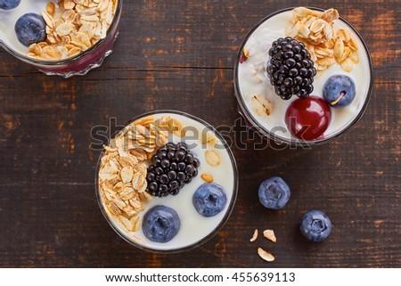 Tree yogurt desserts with berries and muesli. - stock photo