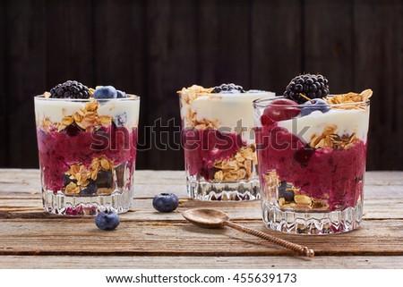 Tree yogurt desserts with fresh berries and muesli. - stock photo