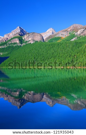 Treeline reflections on Lake Louise of Banff National Park in Canada - stock photo