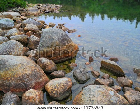 Trees along the far shore are reflected in the boulder-rimmed water of scenic Jordan Pond in Acadia. - stock photo