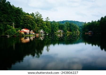 Trees and houses reflecting in Lake Sequoyah, Highlands, North Carolina. - stock photo