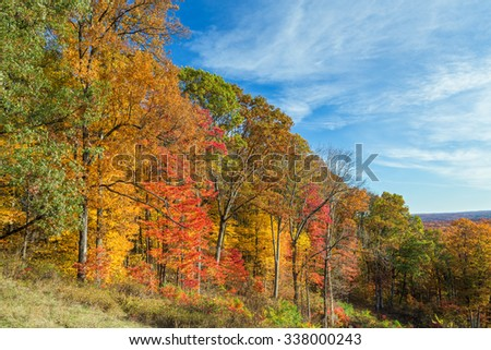 Trees display colorful autumn foliage on hillsides under a cloudy blue sky in Brown County, Indiana. - stock photo