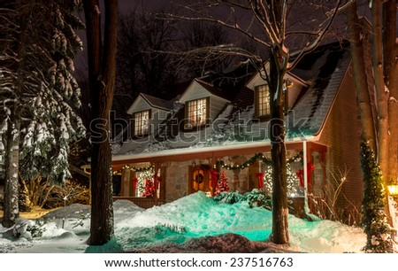 Trees in front of a lighted Christmas Old House with little bit noise grain. - stock photo