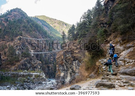 Trekker climing up to Hilary bridge on the way to Namche Bazaar, Everest region, Nepal - stock photo