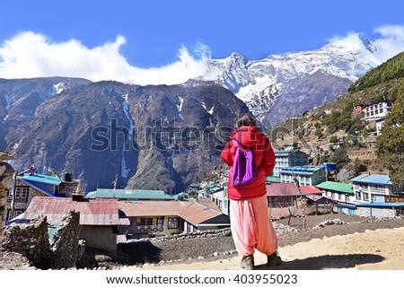 Trekker looking at Namche Bazaar, Himalaya, Nepal - stock photo
