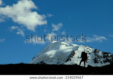 Trekker on the way in the mountains - stock photo