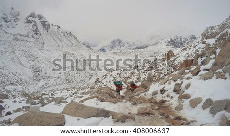 Trekkers and porters in mountains, Porters carrying stuff for trekkers, trekking to the mountain Everest base camp, Himalaya mountains, Himalayan landscape during snow storm, storm in mountains, Nepal - stock photo
