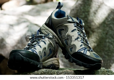 Trekking shoe on stone from a granite - stock photo