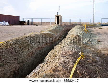trench and outhouse on industrial site - stock photo