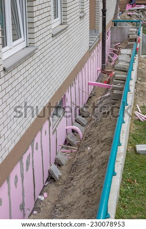 Trenching around building for new layer of foam insulation, fitting styrofoam thermal insulation  - stock photo
