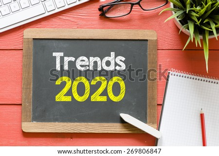 Trends 2020 handwritten on blackboard. Trends 2020 Handwritten with chalk on blackboard, keyboard,notebook,glasses and green plant on wooden background - stock photo