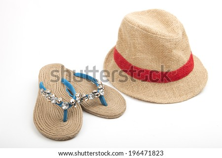 Trendy beachwear with sandals with rope soles and decorated blue thongs alongside a stylish straw hat with red ribbon, on a white background - stock photo