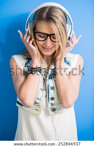 Trendy, blonde girl is listening a music with headphone on blue background. - stock photo