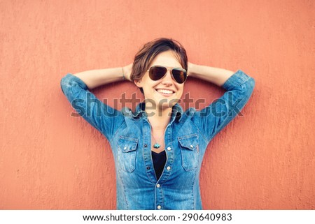 Trendy brunette girl, making face expressions, smiling and laughing against orange background, isolated. Modern lifestyle with beautiful hipster girl with sunglasses - stock photo