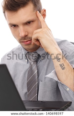 Trendy businessman with tattoo working on laptop computer. - stock photo