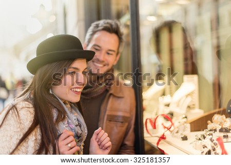 Trendy couple is looking at engagement rings. A grey hair man with beard and a woman with a black hat are standing in front of a jewelry shop. They are looking at the shop window. - stock photo