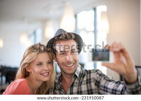 trendy Couple taking a Selfie with a phone, in a coffeeshop - stock photo