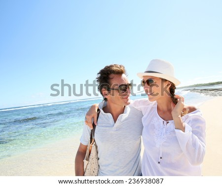 Trendy couple walking on a sandy beach - stock photo