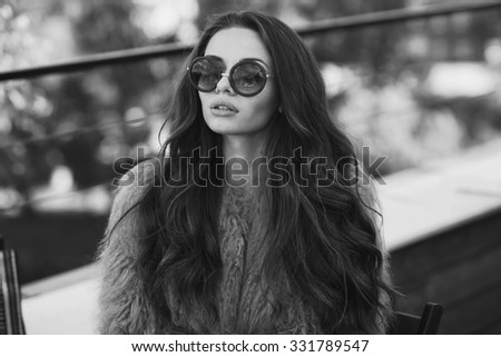 Trendy dressed fashionable girl wearing fur coat. Young pretty beautiful woman with long curly hair looking at you. - stock photo