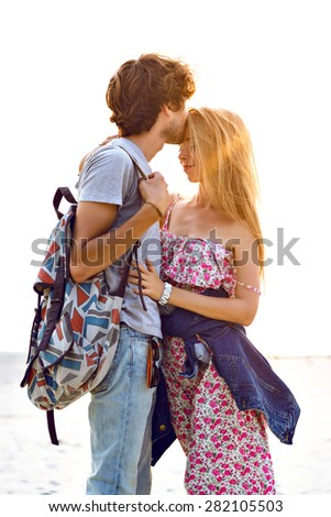 Trendy fashion image of young romantic couple in love wearing stylish hipster vintage clothes, posing at the beach at sunset, love and travel together, positive mood, tender kiss. - stock photo