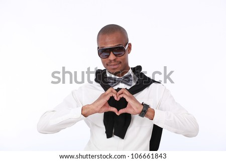 Trendy fashionable African American young man smiling with sunglasses,a silver bow tie,white shirt  and a black jersey, with his hands in the shape of a heart close to his chest on a white background - stock photo