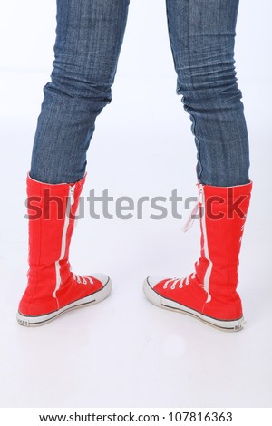 Trendy funky female or male hi top red canvas and white rubber boxing style trainer boots worn with blue jeans and facing backwards with heels showing - stock photo