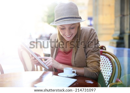 Trendy girl at coffee shop websurfing on internet with tablet - stock photo