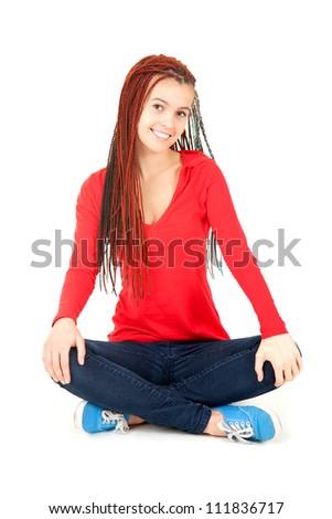 trendy girl sitting on the floor with crossed legs, smiling, full length, white background - stock photo