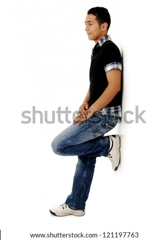 Trendy guy standing against the wall and smiling - stock photo