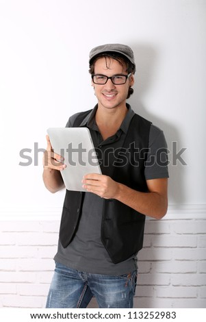 Trendy guy using electronic tablet leaning on wall - stock photo