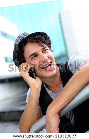 Trendy guy with hat talking on mobile phone - stock photo