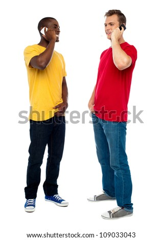 Trendy handsome guys attending call on cellphone. Full length portrait - stock photo