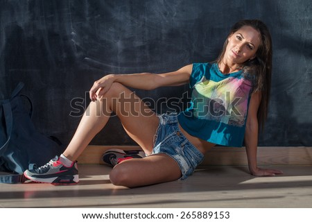 Trendy Hipster Girl in jeans shorts and t-shirt Sitting on the floor looking at the camera. - stock photo