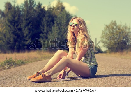 Trendy Hipster Girl Sitting on the Road. Toned Photo. Modern Youth Lifestyle Concept. - stock photo
