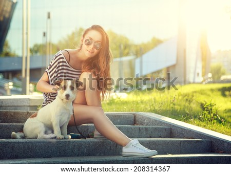 Trendy Hipster Girl with her Dog on Urban Background. Toned and Filtered Photo. Modern Youth Lifestyle Concept. - stock photo