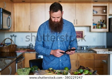 trendy man with cool beard using tablet or smartphone to look up taco recipe in kitchen shot with selective focus - stock photo