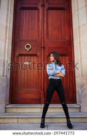 Trendy model posing on the street near building and confidently looking sideways,female holding arms crossed standing against wooden brown color door background with copy space for your text message - stock photo