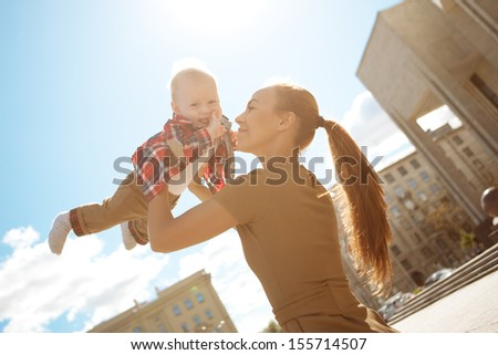 Trendy modern mother on a city street with a pram. Young mother walks with a child in the city. Beautiful young woman with a child in a baby carriage - stock photo
